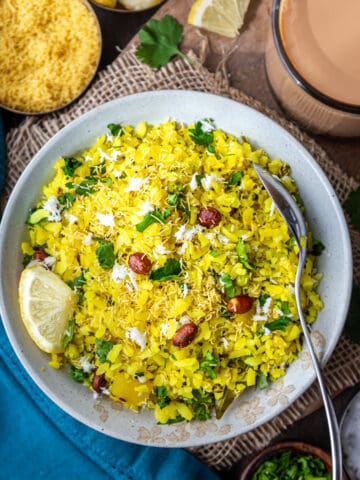 Plate of Poha garnished with cilantro, coconut and sev witth chai on side
