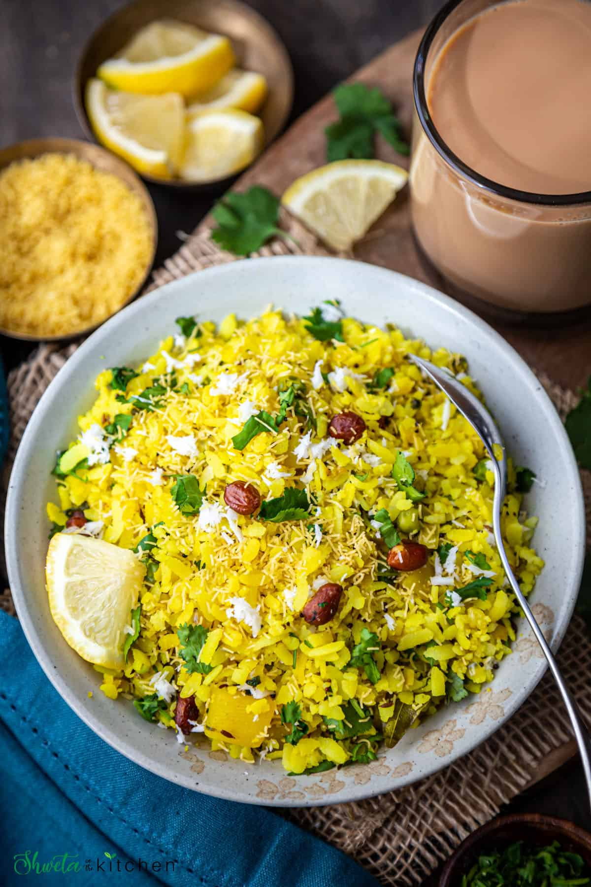 Plate of kanda batata poha with cup of chai on the side