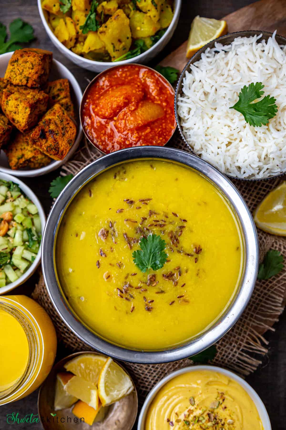 Bowl of Varan, rice, bhaji, pickle, kothimbir vadi, salad, ghee, lemon and mango shrikhand on side