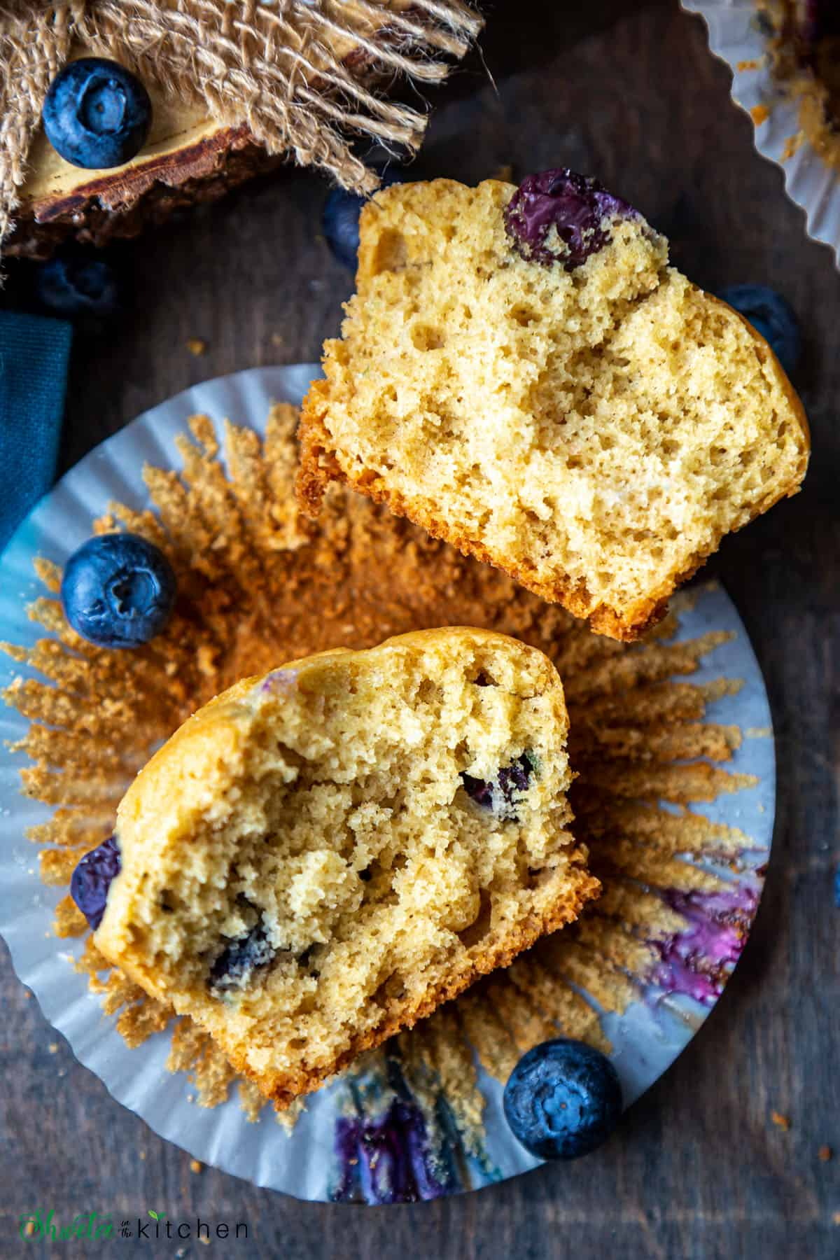 Blueberry muffin split in half showing the crumbs and texture
