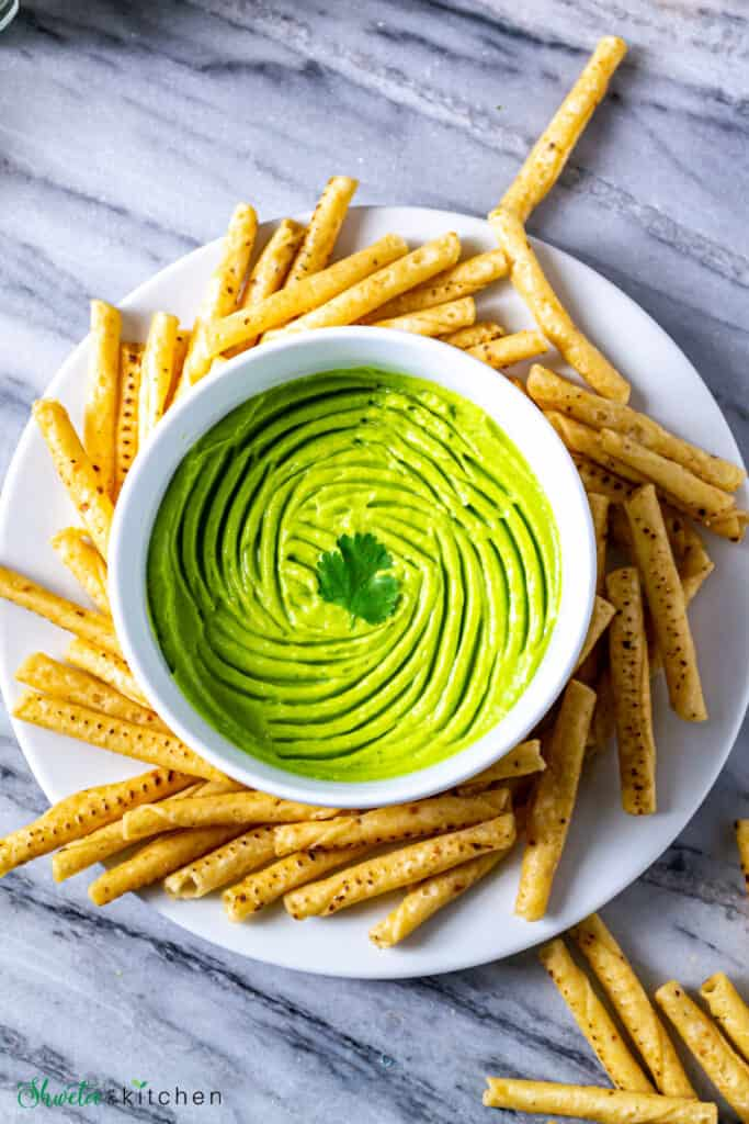 Avocado dip in a bowl on a plate of breadsticks and garnished with fresh coriander