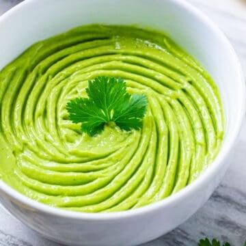 Creamy avocado dip in a white bowl garnished with a fresh parsley leaf