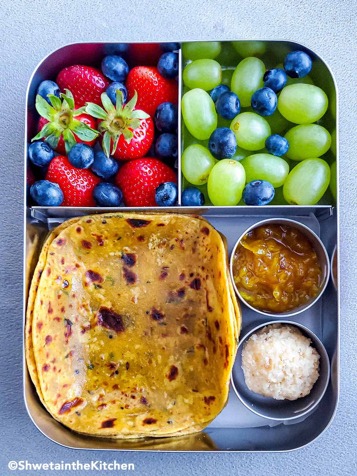 Dal paratha in lunchbox with fruits, chutney and ladoo