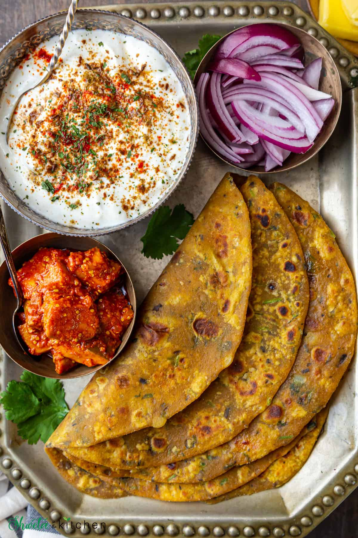 Dal paratha, pickle, spiced yogurt and onions on a tray