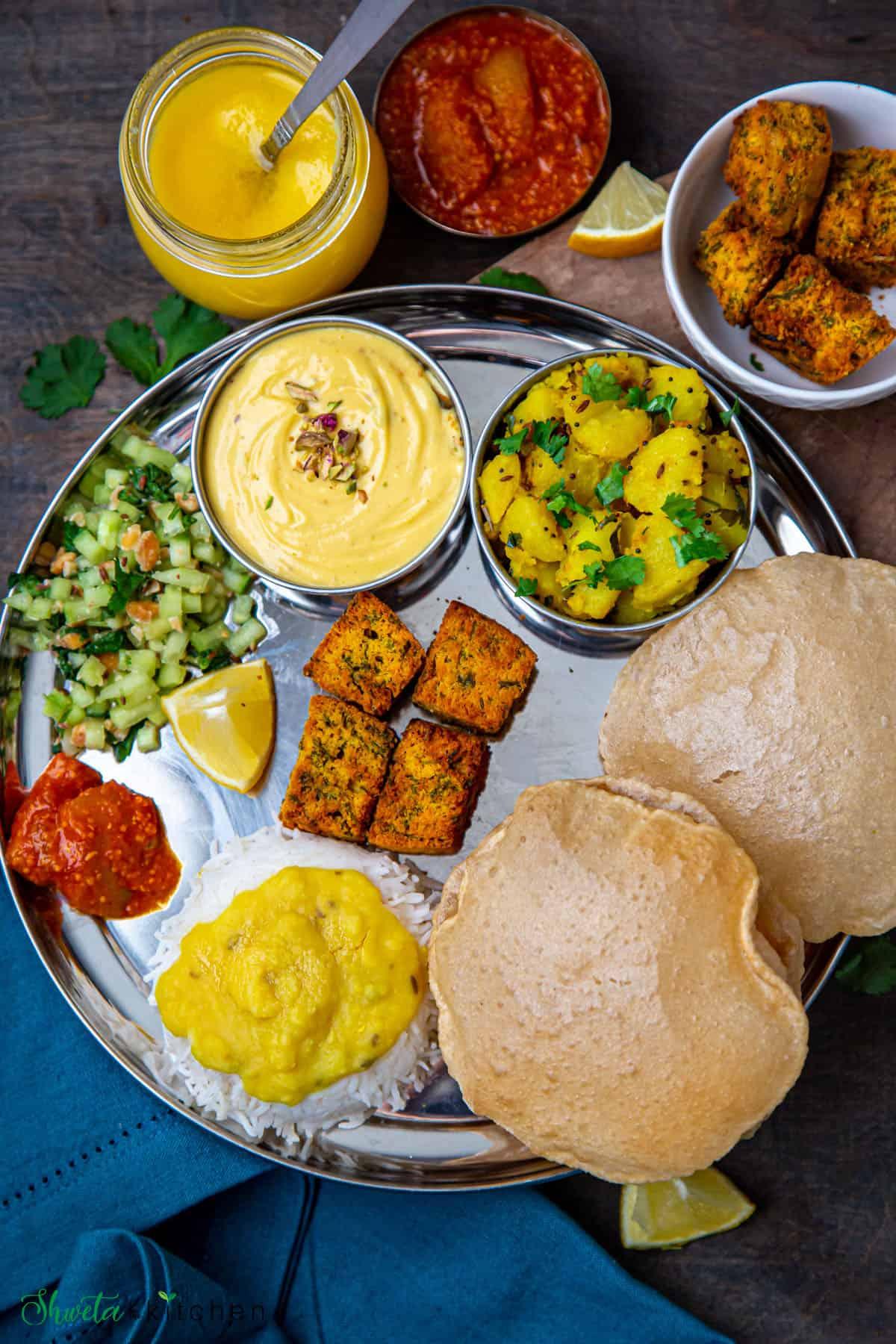 Maharashtrian thali for gudi padwa with koshimbir, varan bhaat, batata bhaji, poori, shrikhand