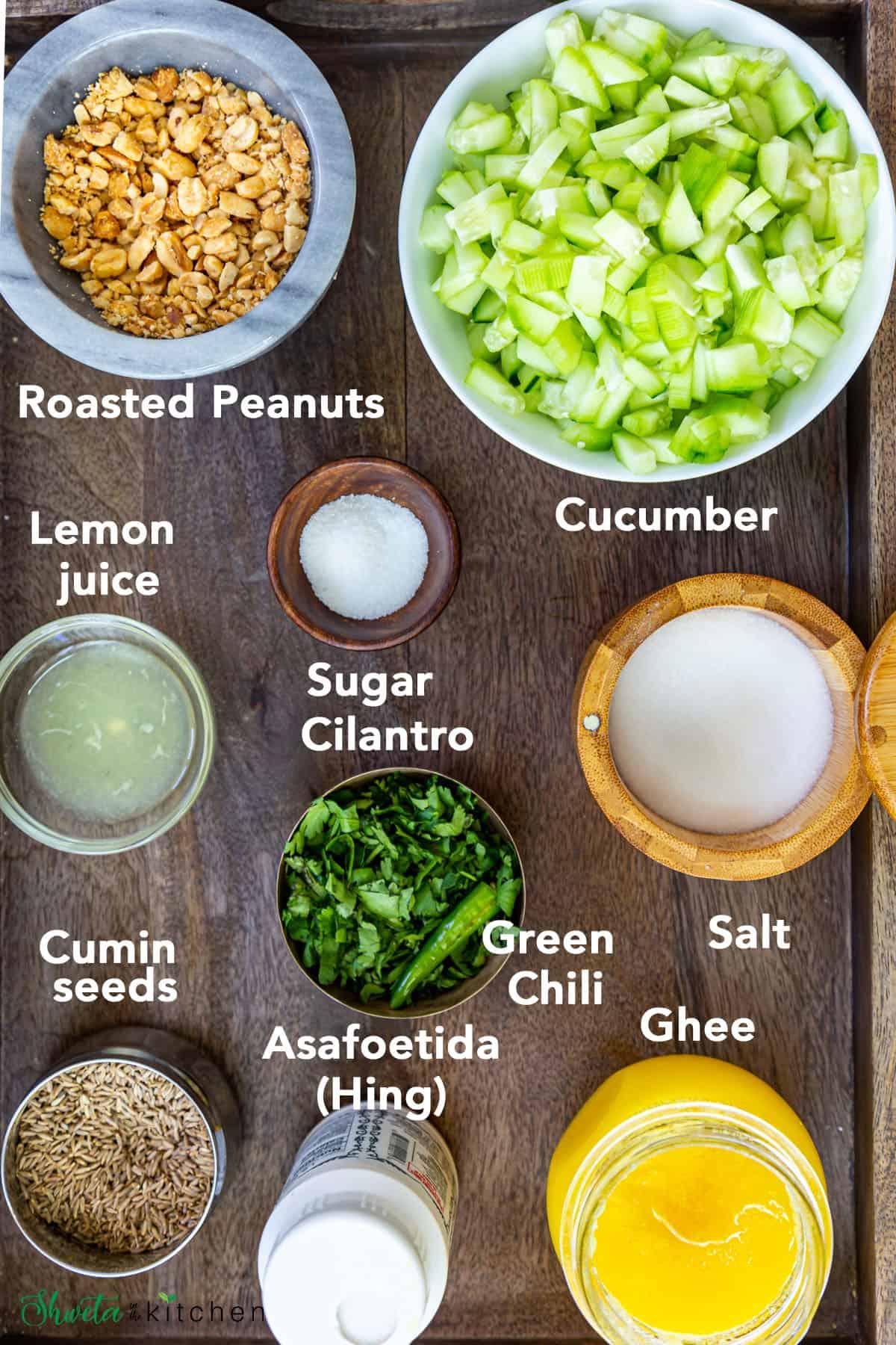 Ingredients for kakdi chi koshimbir in bowls on wooden base