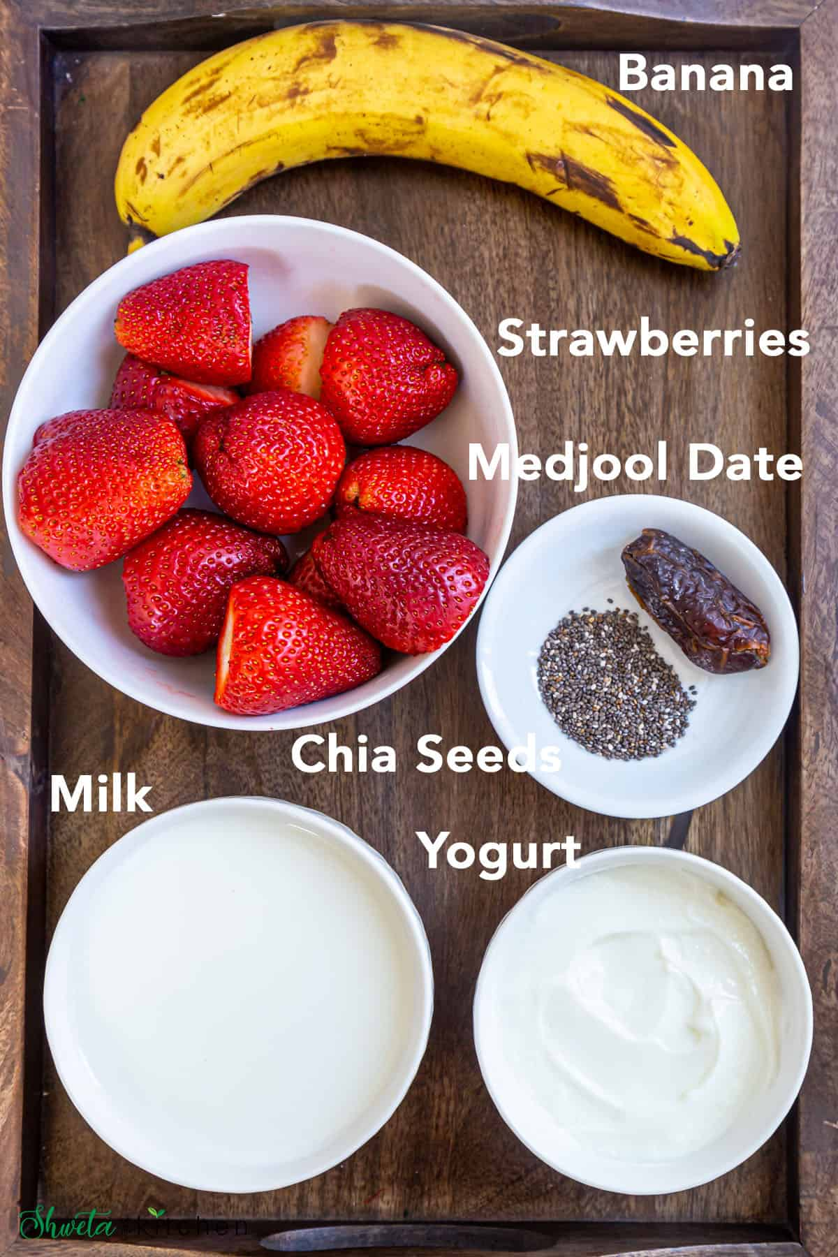 Strawberry banana smoothie ingredients in white bowls on a wooden tray