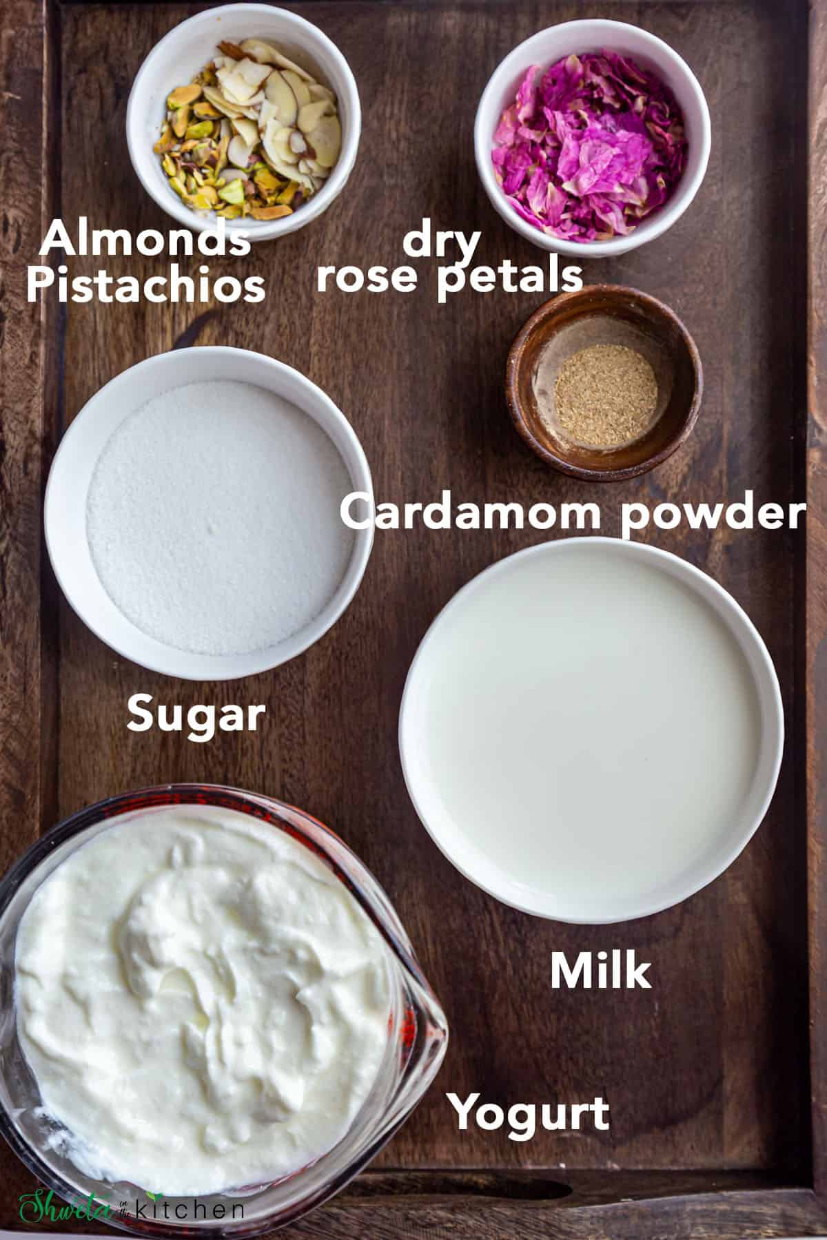 Sweet lassi ingredients in bowls on wooden tray