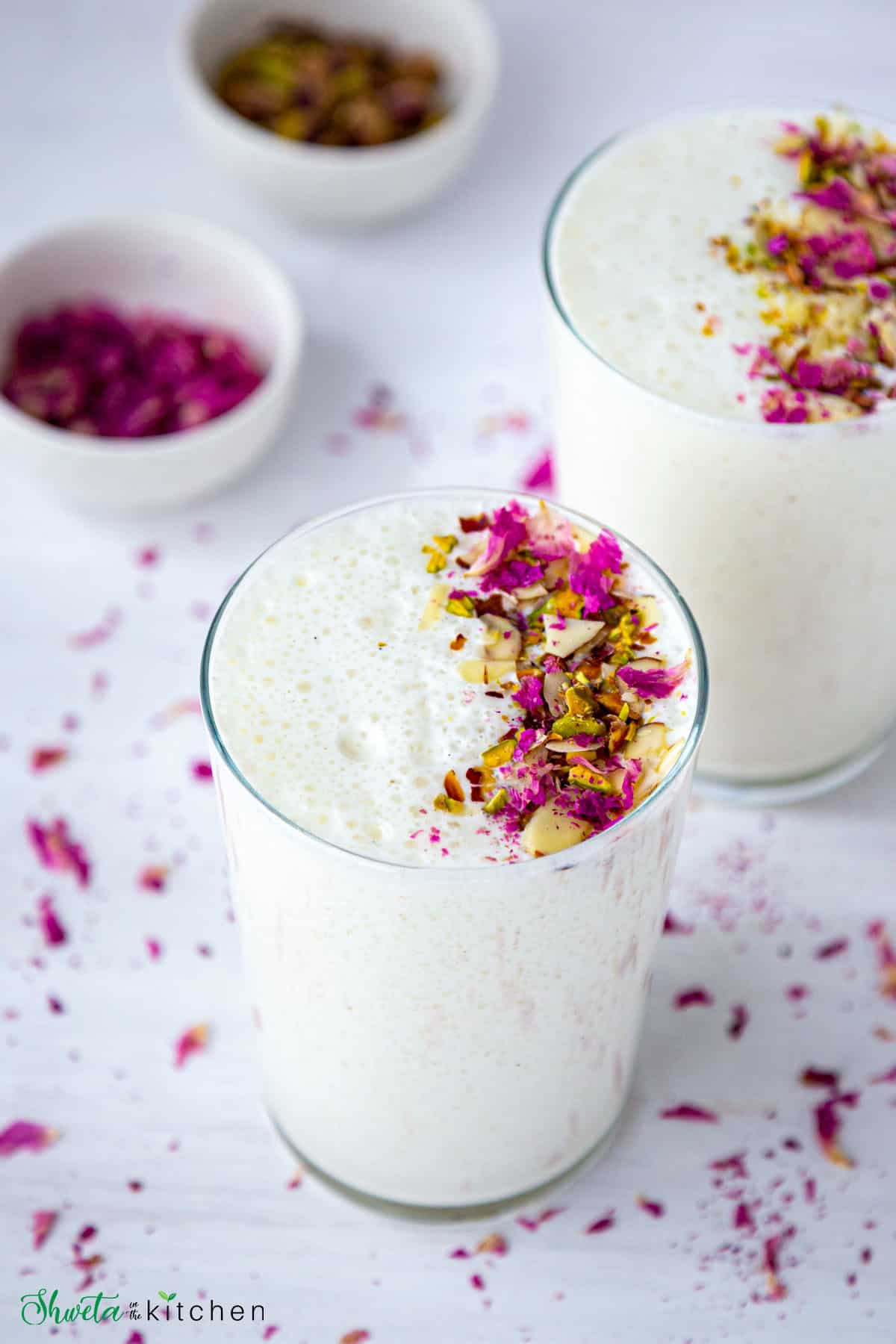 Two glass full of sweet lassi drink garnished with nuts and rose petals
