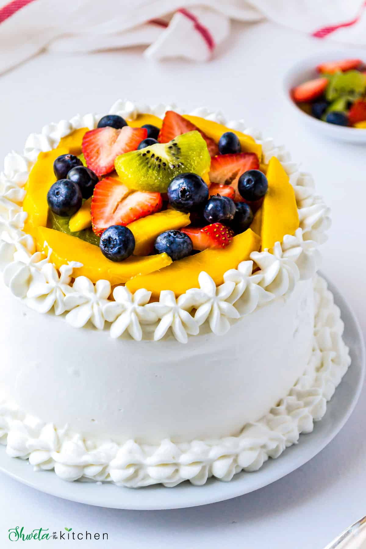 Close up of Vanilla Cream Sponge Cake topped with fresh fruits on a white plate