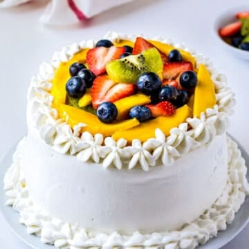 Layered Vanilla Sponge Cake frosted with Whipped Cream and topped with fresh fruits