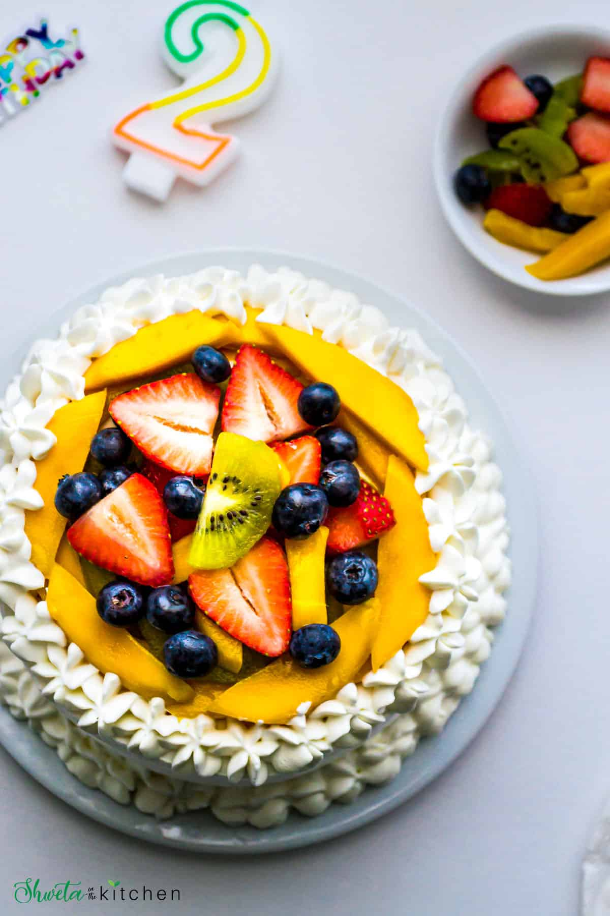 Vanilla Sponge Cake with Whipped Cream frosting and number 2 candle and more fruits on side
