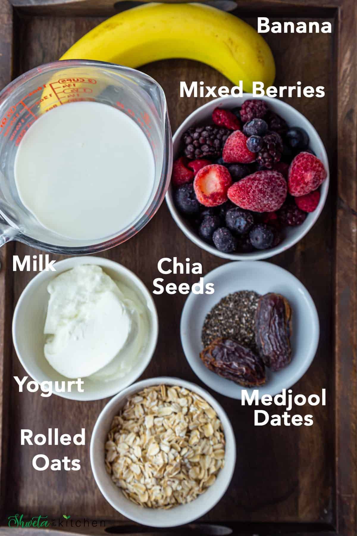 Berry Oat smoothie ingredients in white bowls on a wooden tray