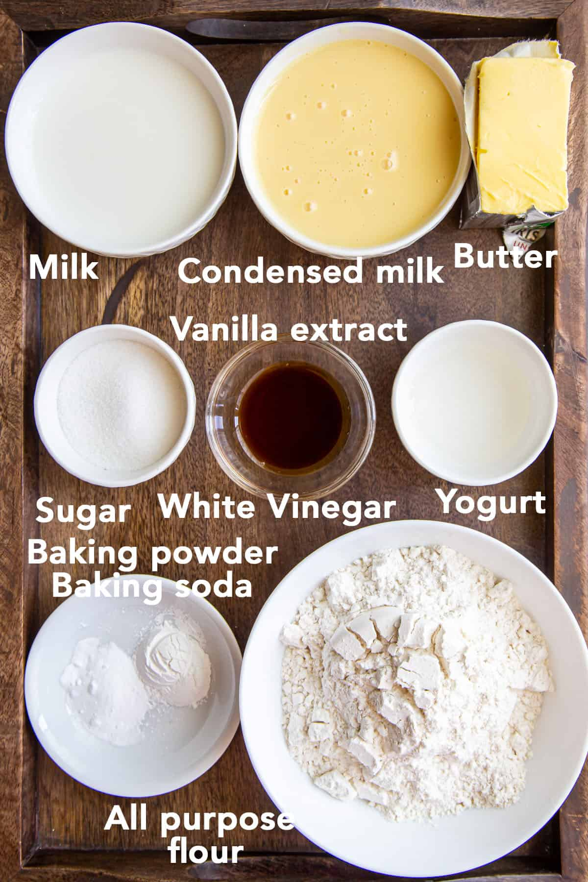 Ingredients for Eggless Vanilla Sponge Cake in bowls on wooden surface