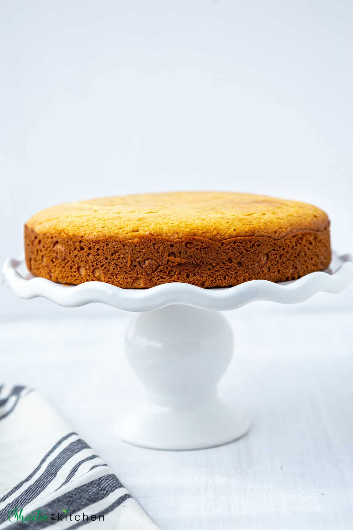 Top view of eggless vanilla sponge cake on a white cake stand
