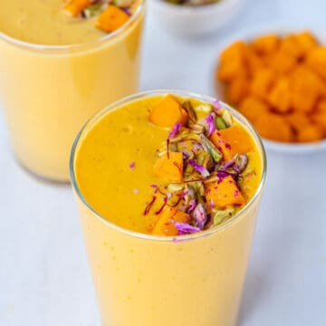 Mango lassi in tall glasses garnished with mangoes and nuts