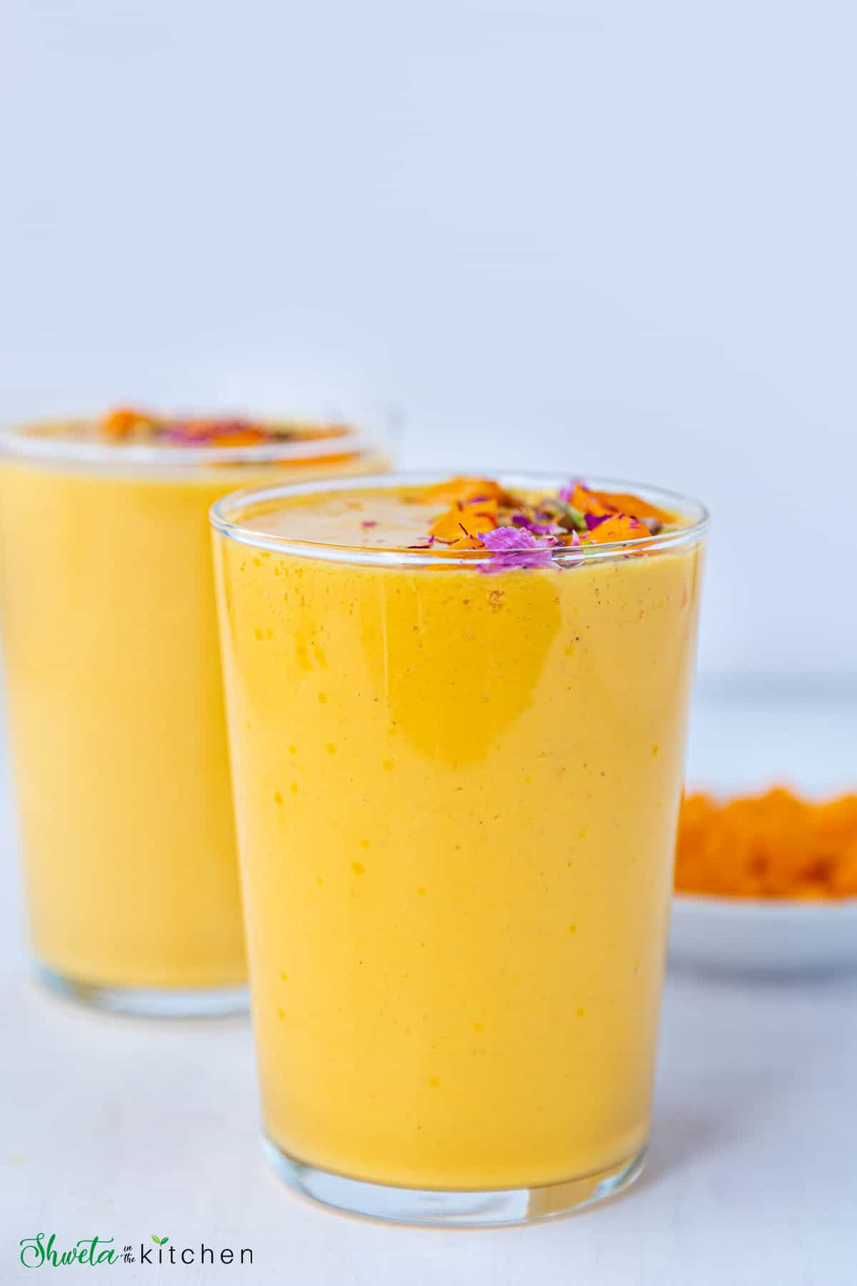 Front view of Mango lassi in tall glasses garnished with mangoes and nuts