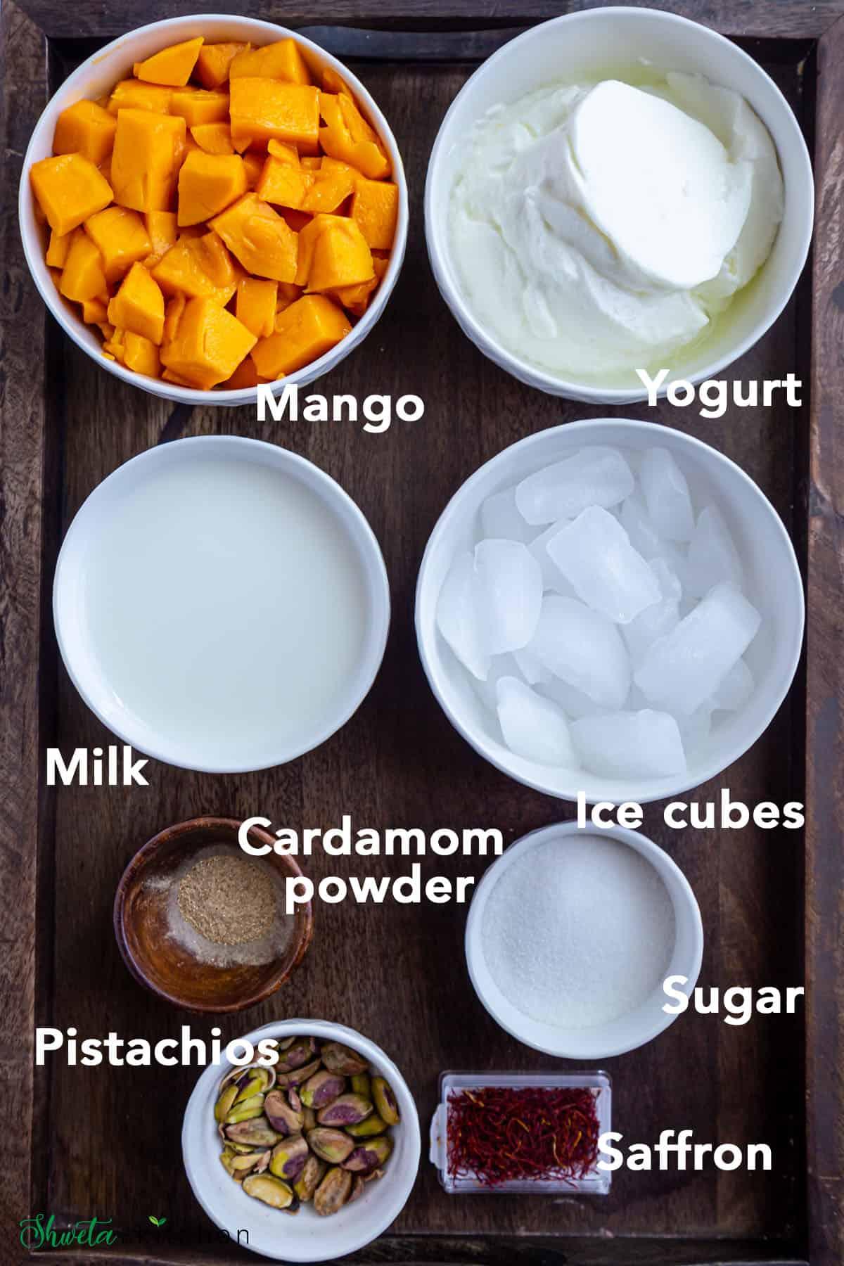 mango lassi ingredients in a bowl on a wooden board