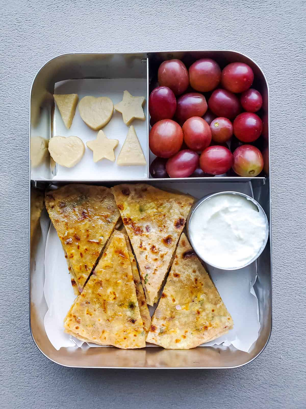 Aloo Paratha with grapes and Indian sweet in stainless steel  lunchbox