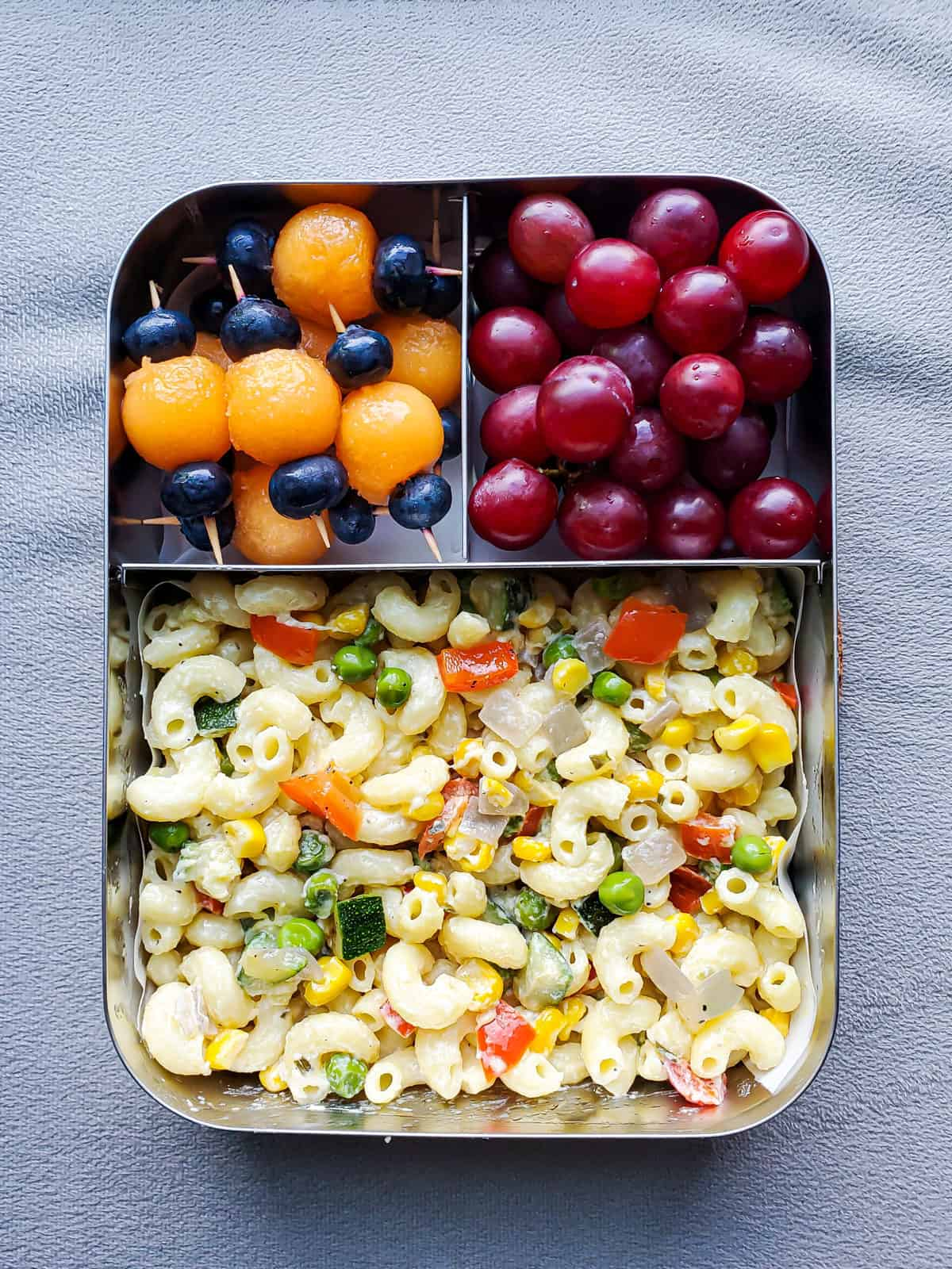 Creamy Garlic Pasta with veggies with fruits in a stainless steel lunchbox