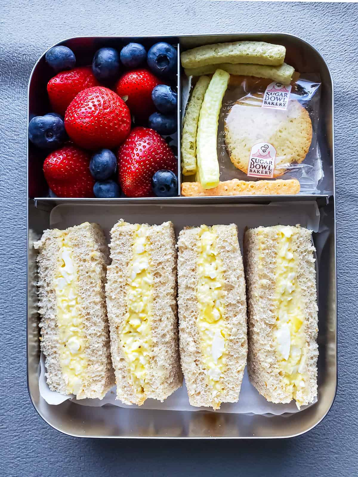 Egg Salad finger sandwiches with berries and sweet treat in stainless steel lunchbox