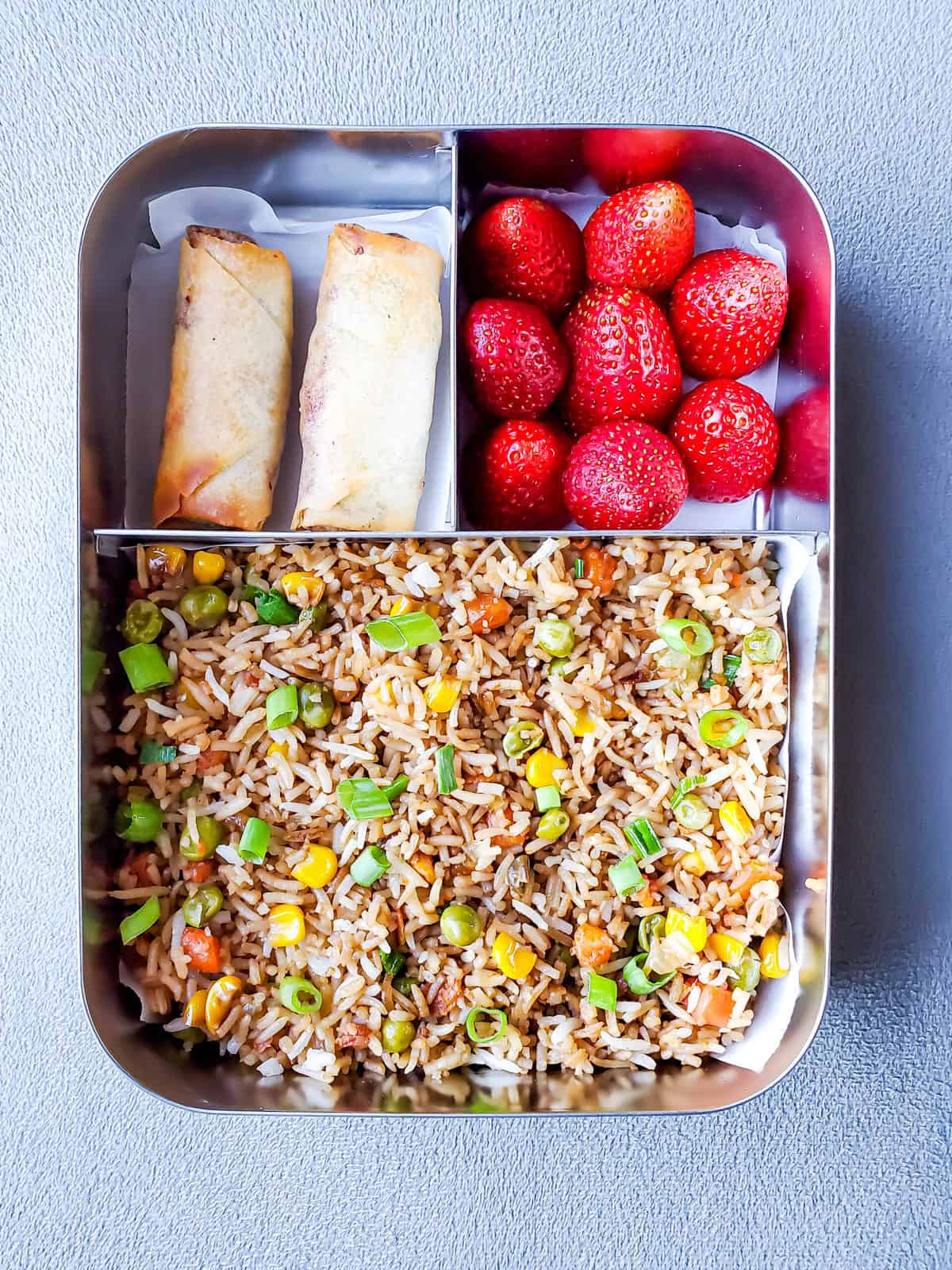 Veg Fried rice and spring rolls and strawberries in lunch box