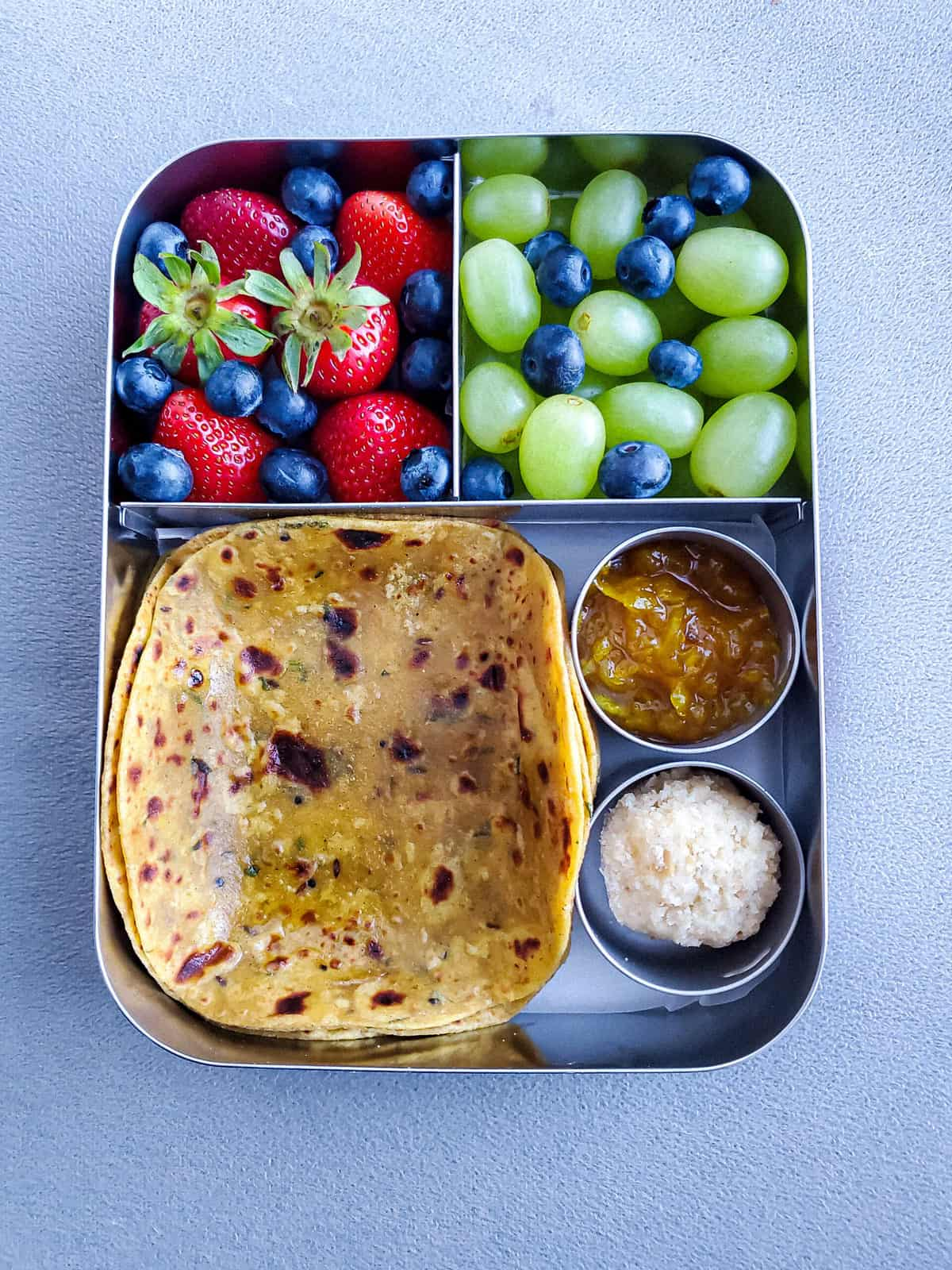Leftover Dal Paratha with fruits and ladoo in stainless steel Lunchbox