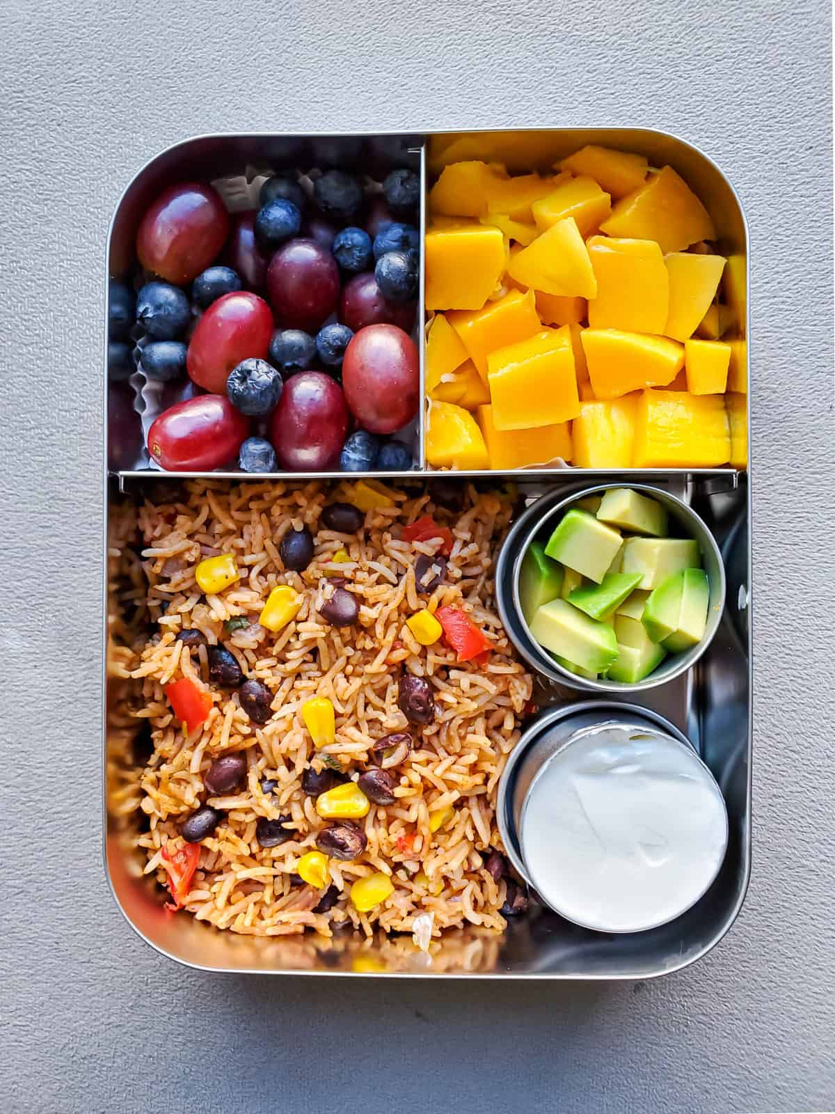 Mexican Rice with black beans and corn, mango, avocado and sour cream on side in Lunchbox