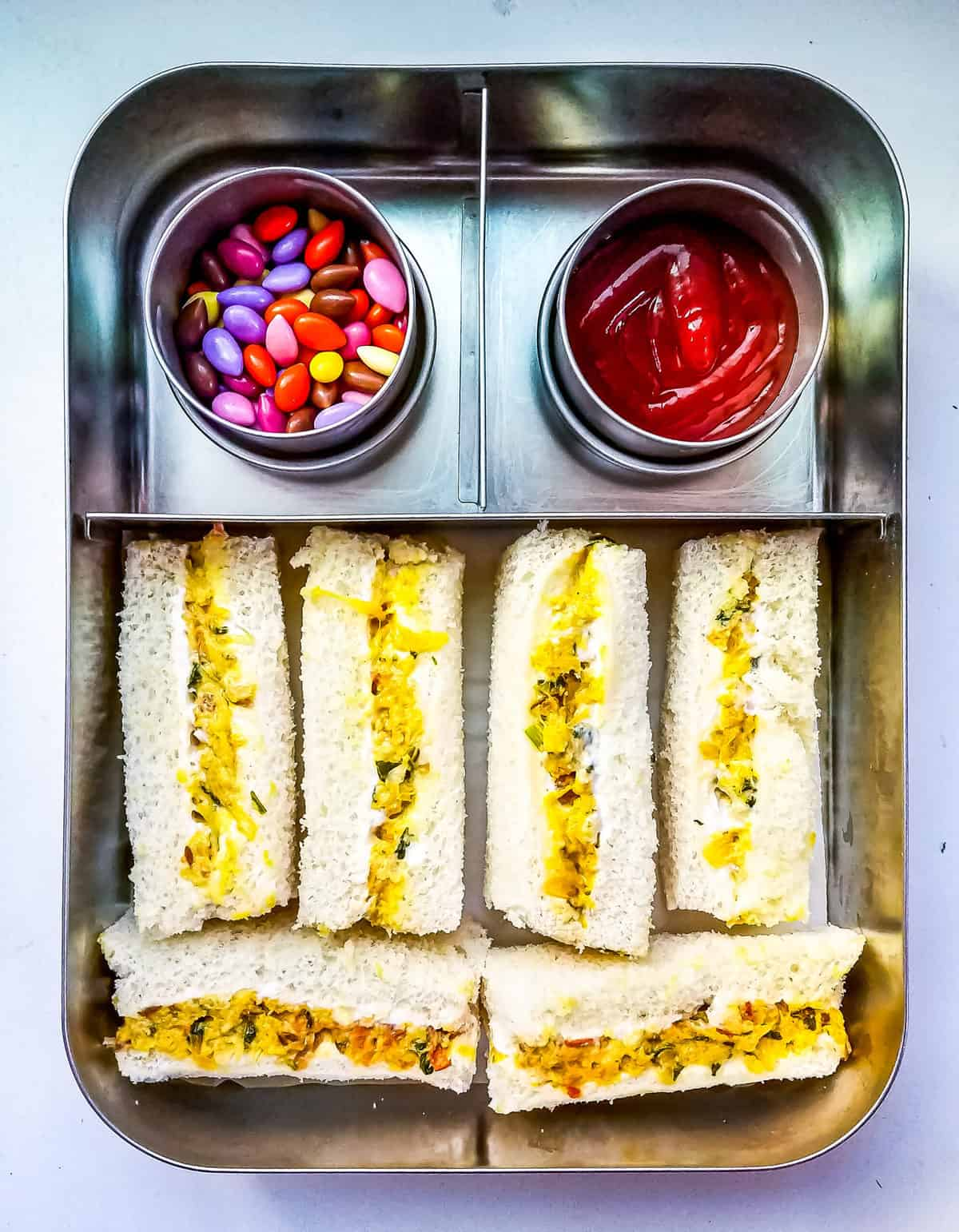 Paneer Bhurji finger sandwiches with ketchup and treat in stainless steel lunchbox