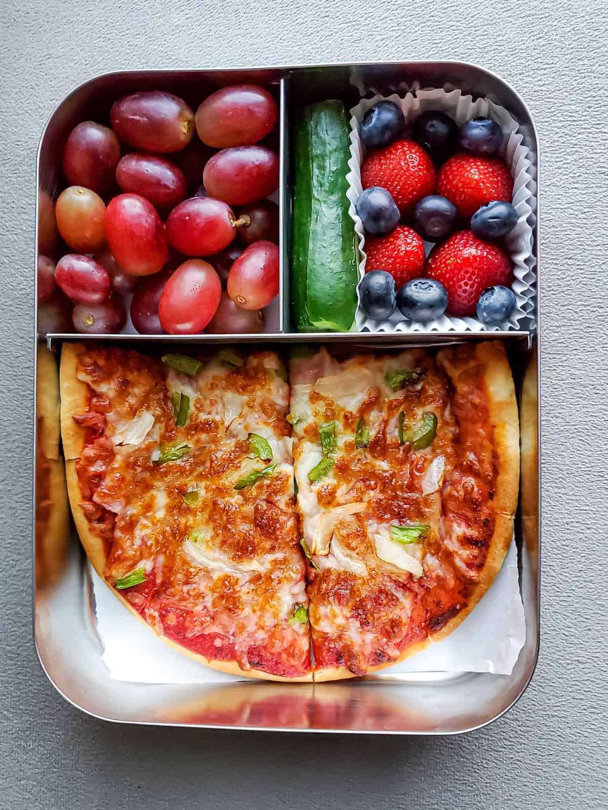 School lunch box with veggie Pita Bread Pizza, fruits and cucumber