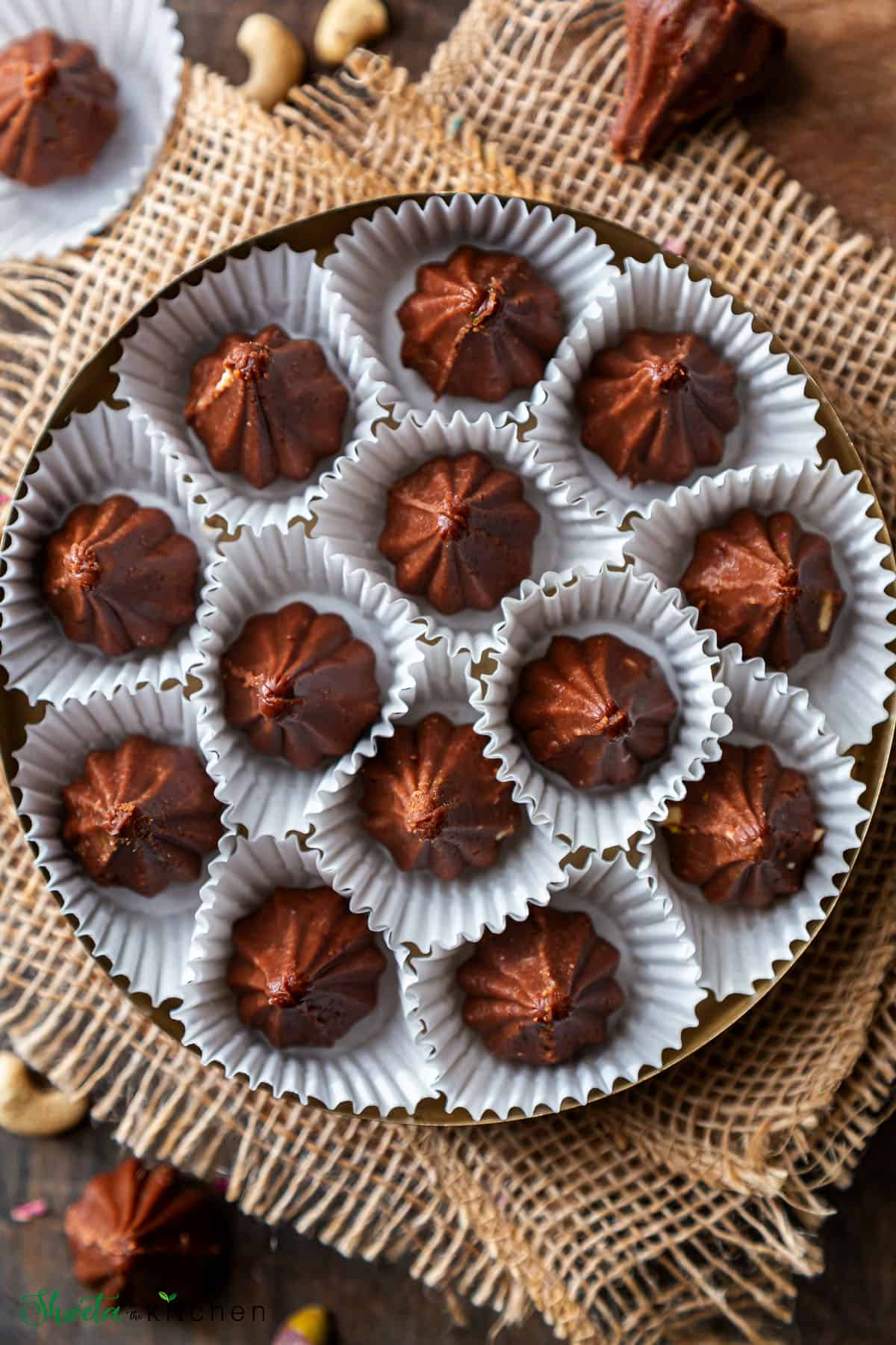 Top view of Chocolate modak in white wrappers arranged on a plate in circular pattern