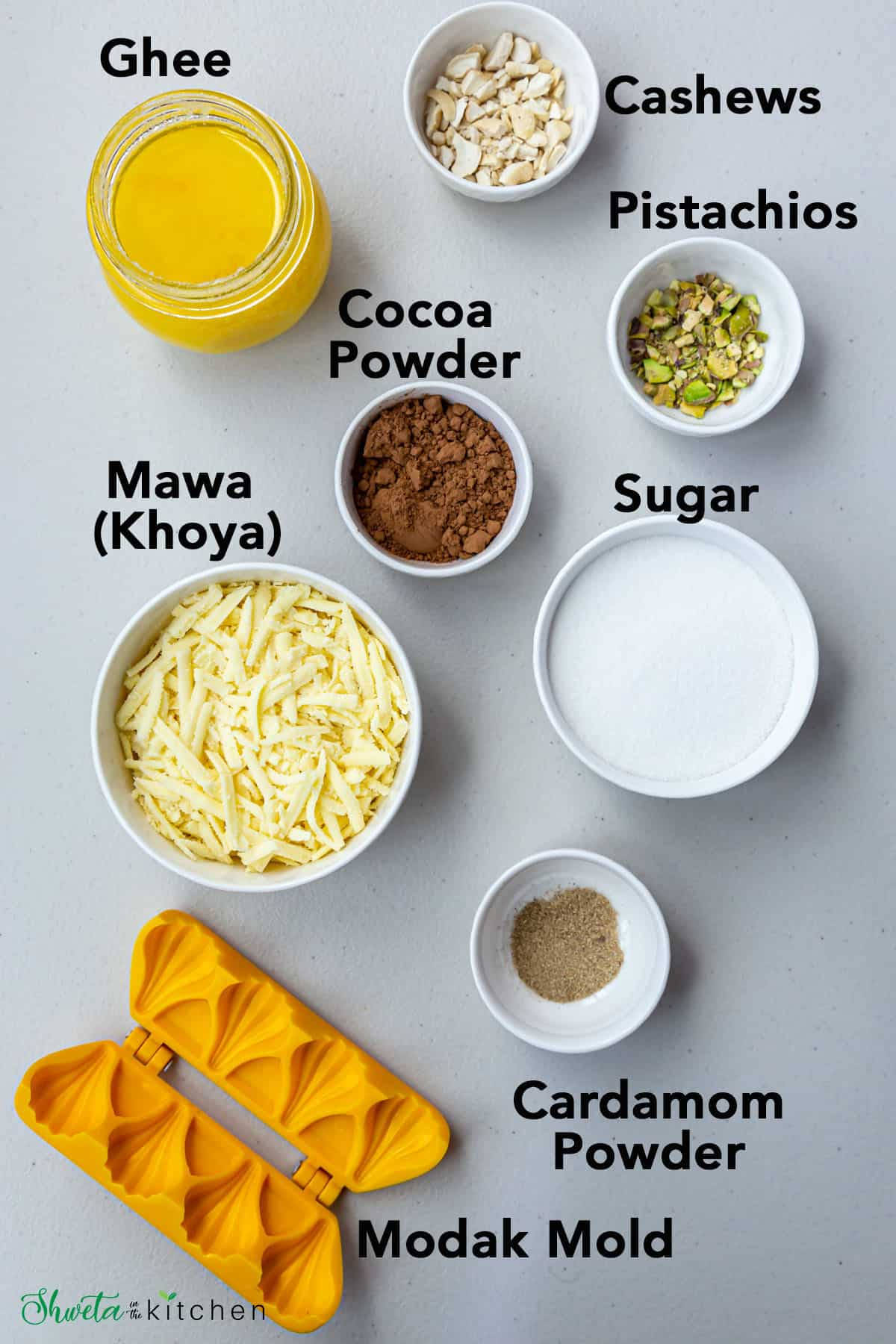 Chocolate Modak Ingredients in bowls aalong with yellow modak mold n white gray surface